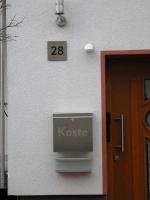 Elegante Hausnummer aus Edelstahl mit schwarzem Plexiglas hinterlegt