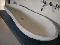 handgemeißeltes Waschbecken und ein hinterleuchteter Spiegel vom Allerfeinsten