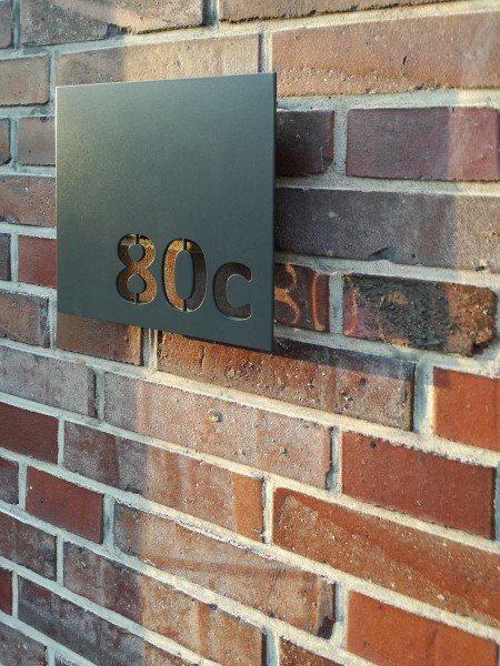 Hausnummer mit negativ geschnittener Schrift