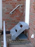 Treppe aus feuerverzinktem Stahl mit Gitterroststufen und einem Handlauf