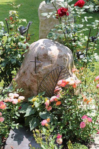 Grabstelle mit einem Findling und einer Textafel und Rankgitter aus Tombak