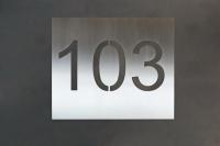 Hausnummer 103 mit negativ geschnittener Schrift