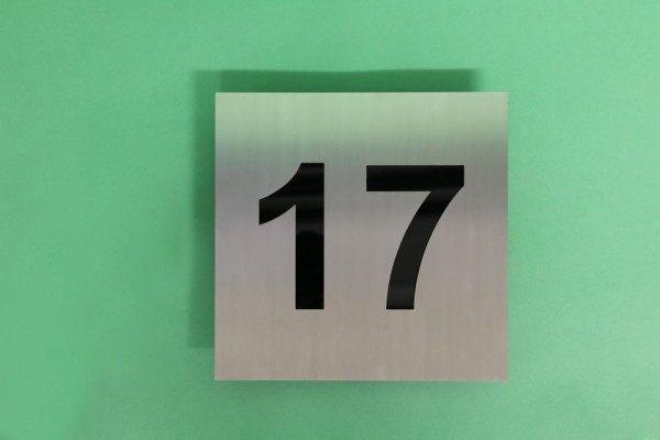 Hausnummer 17 aus Edelstahl mit schwarzem Acrylglas hinterlegt