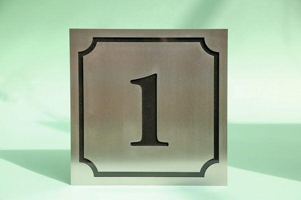Hausnummer 1 mit schwarzem Plexiglas hinterlegt