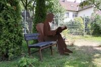Bank mit rostiger Skulptur in Lebensgröße
