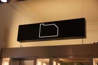 Gelasertes, hinterleuchtetes Logo über der Theke in der Gästeresidenz PelikanViertel