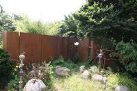 Wand und Sichtschutz aus rostigem Stahl mit integriertem Grill und einem Räucherofen