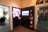 Monitorwand mit integriertem Prospekthalter und Regalfächern aus Stahl für das Helmut Kohl Haus in Hildesheim