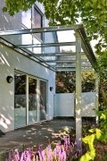 Terrassendach mit einem seitlichen Sichtschutz und Windschutz