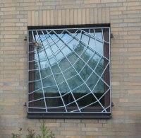 Fenstergitter und Tor in Form eines Spinnennetzes