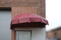 Vordach in Form eines kaputten Regenschirms