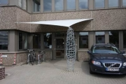 Vordach zum Vewaltungsgebäude der SOCON SONAR CONTROL Kavernenvermessung GmbH mit einer Säule in Schmitzstruktur und einem Segel