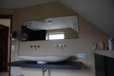 Badezimmer mit handgemeißeltem Waschbecken und einem hinterleuchteten Spiegel