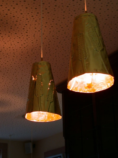 Abgependelte Leuchten aus vergoldeter Kupferfolie für den Brasseriebereich im Kalimera