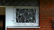 Fenstergitter mit Aststruktur und Vögeln