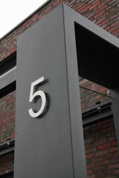 gelaserte Hausnummer aus Edelstahl an einem Vordach aus Stahl