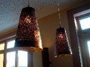 Abgependelte, gelochte Leuchten aus vergoldeter Kupferfolie für den Brasseriebereich in Kalimera